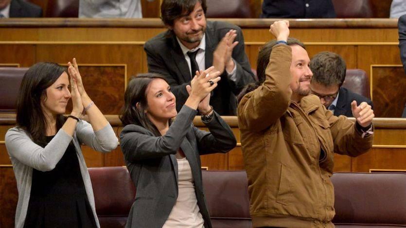 Los dirigentes de Podemos saludan a la tribuna de invitados, donde miembros de la FELGTB asistían al debate