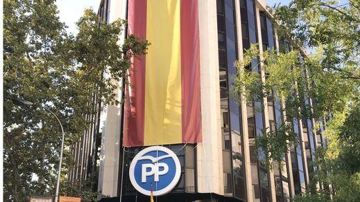 El PP cubre su sede con una enorme bandera de España
