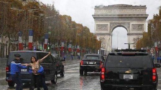Una activista de Femen intenta abalanzarse sobre el coche de Trump durante la celebración del Armisticio