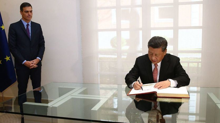 El presidente de la República Popular de China, Xi Jinping, firma en el Libro de Honor de La Moncloa en presencia del presidente del Gobierno, Pedro Sánchez