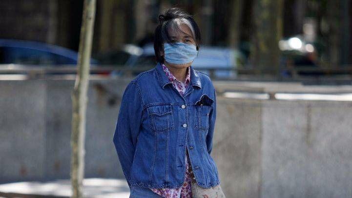 Una turista japonesa con mascarilla para evitar la contaminación atmosférica en el paseo de la Castellana de Madrid