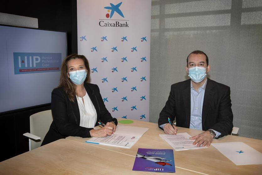 Ana Díez Fontana, directora ejecutiva de Negocios y Emprendedores de CaixaBank, y Albert Planas, CEO de Nebext, empresa organizadora del HIP, durante la firma del acuerdo de participación de la entidad como banco oficial del salón