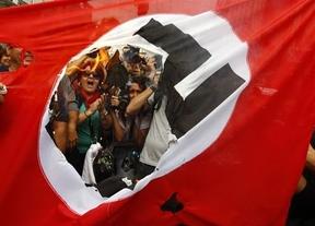 Granadas aturdidoras, gases lacrimógenos y quema de banderas nazis 'reciben' a Merkel en Atenas